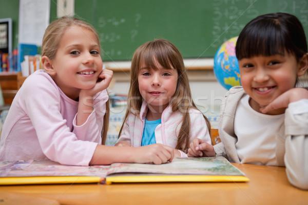 Feliz colegialas lectura cuento de hadas compañero de clase mirando Foto stock © wavebreak_media