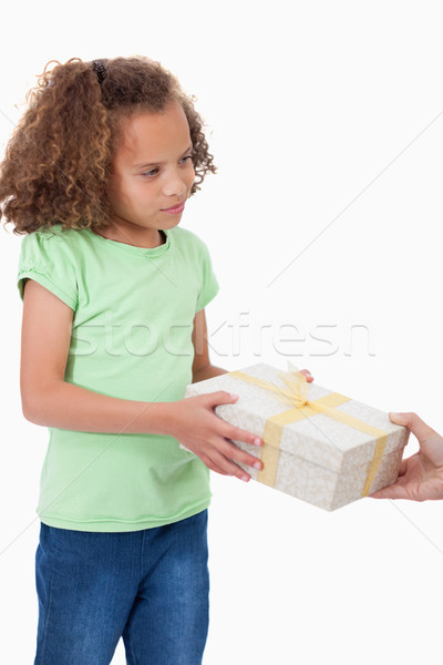 Stock photo: Portrait of a young girl receiving a gift against a white background