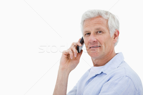 Side view of a man making a phone call while looking at the camera against a white background Stock photo © wavebreak_media