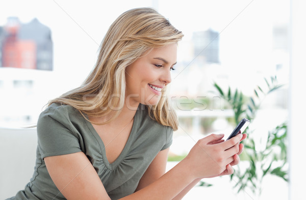 A woman turned to the side, smiles as she sits and uses her phone. Stock photo © wavebreak_media