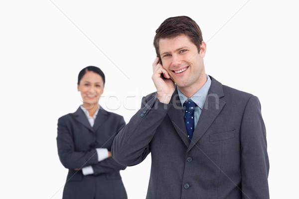 Sorridente vendedor telefone colega atrás Foto stock © wavebreak_media