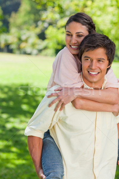 Woman smiling while holding her friends shoulders tight as he is carrying her on his back in a park Stock photo © wavebreak_media
