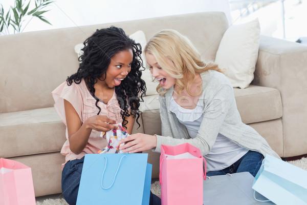 Két nő ül padló néz ruházat bevásárlótáskák Stock fotó © wavebreak_media
