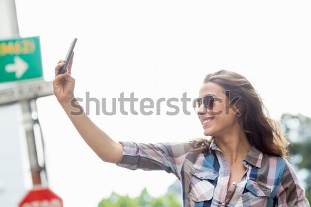 Portrait of a Latin student surprised while using a smartphone against white background Stock photo © wavebreak_media