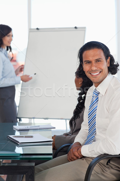 Stock photo: Smiling businessman sitting with hands crossed while listening to a presentation