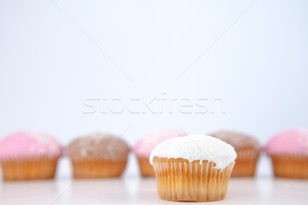 Muffin placed in front of a line of muffin with icing sugar against a blue background Stock photo © wavebreak_media
