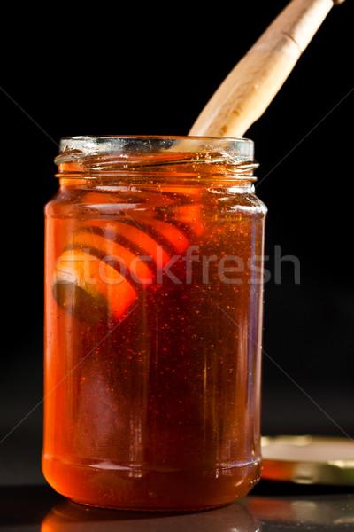 Honey full jar with a honey dipper against a black background Stock photo © wavebreak_media