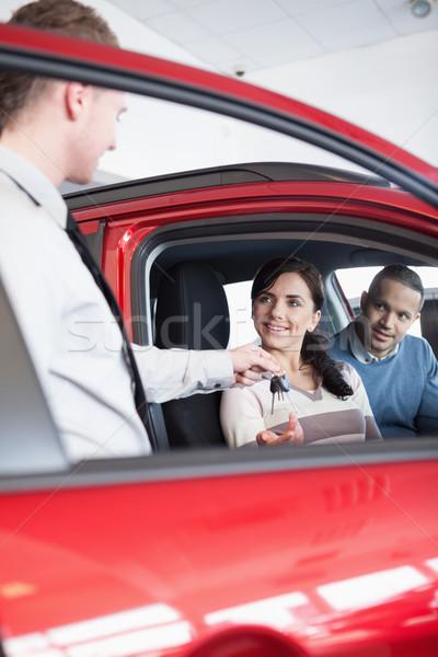 улыбаясь клиентов ключи от машины продавцом пару Palm Сток-фото © wavebreak_media