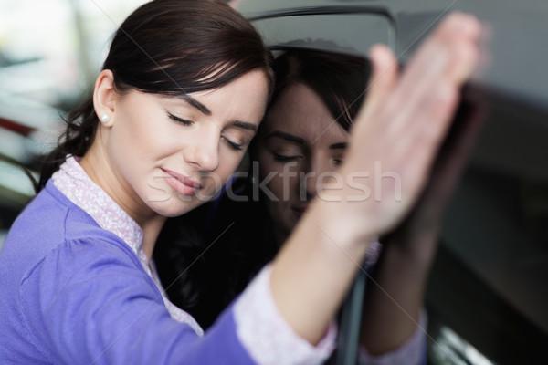 Woman resting on a car in a car dealership Stock photo © wavebreak_media