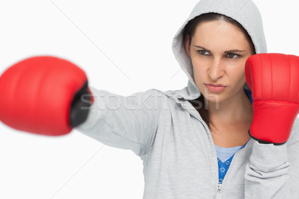 Combative brunette in sweatshirt boxing against white background Stock photo © wavebreak_media