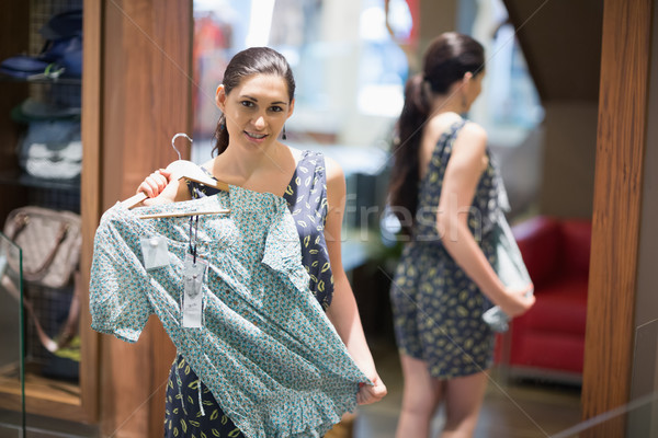Woman holding up shirt in clothes store Stock photo © wavebreak_media