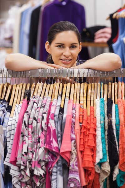 Stock photo: Woman leaning on a clothes rack and smiling in a boutique