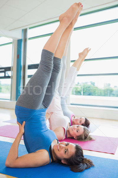Stock photo: Smiling women stretching backs at yoga class in fitness studio