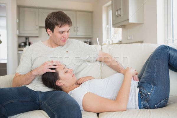 Prospective parents lying on the couch together in living room Stock photo © wavebreak_media