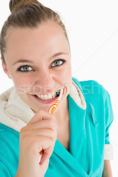 Smiling woman with bathrobe washing her teeth in the white background Stock photo © wavebreak_media