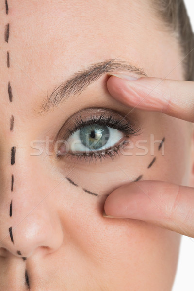 Woman with face lift marker on her face stretching her eye out Stock photo © wavebreak_media