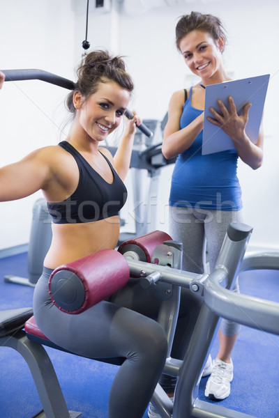 Stock photo: Happy female trainer and client on weights machine