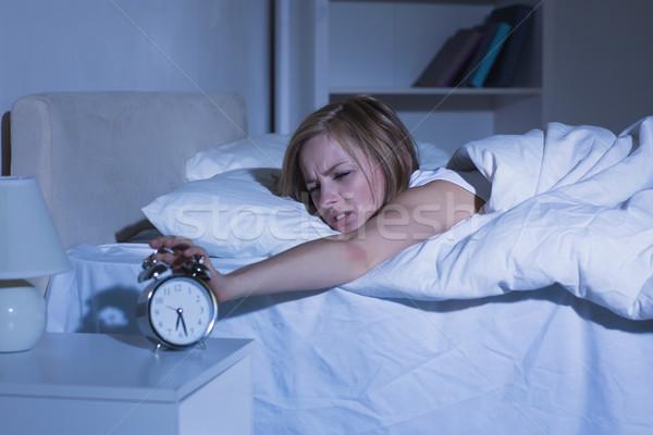 Nő ágy kéz ébresztőóra ingerült fiatal nő Stock fotó © wavebreak_media