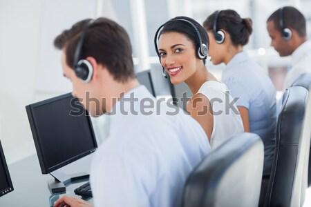 Atractivo call center empleado mirando hombro Foto stock © wavebreak_media