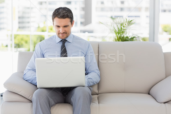 Well dressed man using laptop at home Stock photo © wavebreak_media