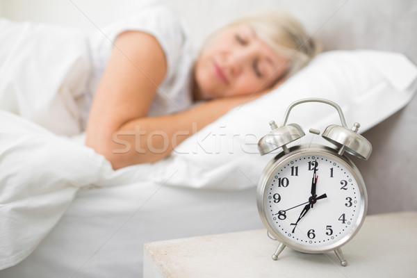 Nő alszik ágy ébresztőóra előtér hálószoba Stock fotó © wavebreak_media