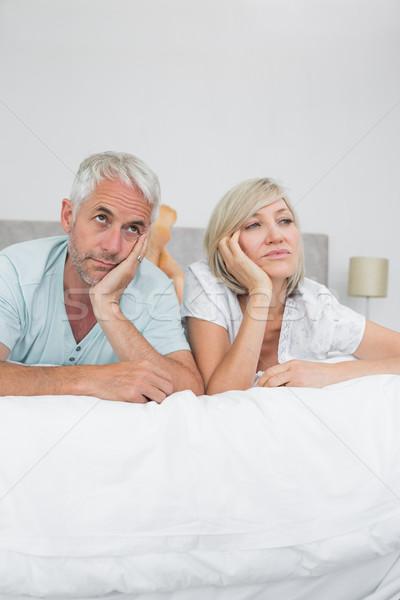 Displeased mature man and woman lying in bed Stock photo © wavebreak_media