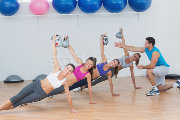 Instructor assisting fitness class with kettlebells Stock photo © wavebreak_media