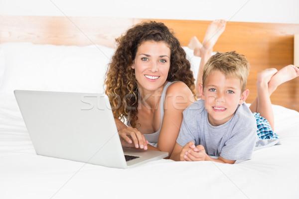 Sonriendo nino madre cama usando la computadora portátil Foto stock © wavebreak_media