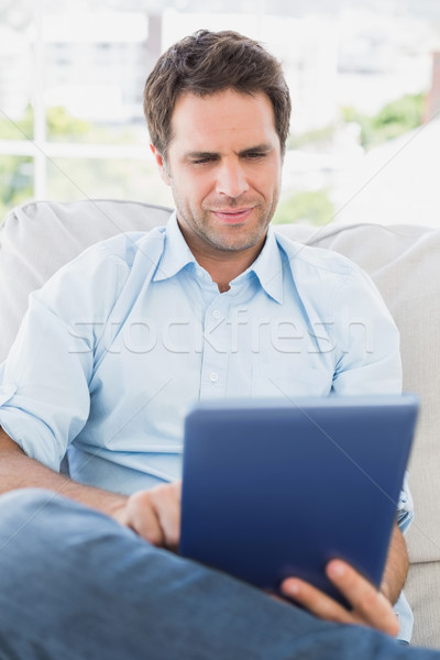 Focused man sitting on the couch using his tablet Stock photo © wavebreak_media