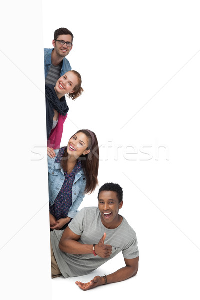 Portrait of four happy young friends with blank board Stock photo © wavebreak_media