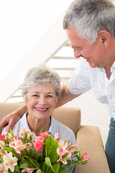 Senior man giving his partner a bouquet of flowers smiling at ca Stock photo © wavebreak_media