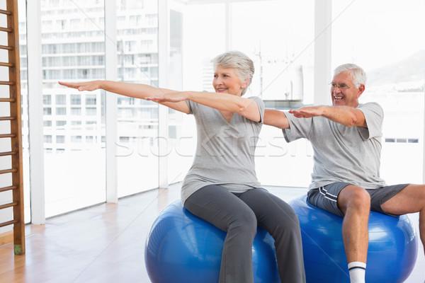 Senior couple doing stretching exercises on fitness balls Stock photo © wavebreak_media