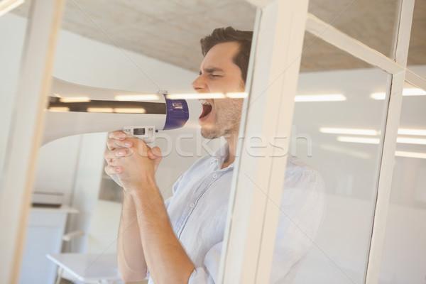 Casual businessman shouting through megaphone Stock photo © wavebreak_media