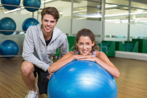Fit woman leaning on exercise ball with trainer smiling at camer Stock photo © wavebreak_media