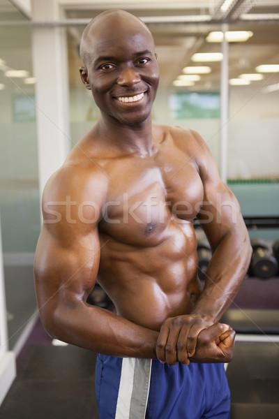 Uśmiechnięty półnagi muskularny człowiek stwarzające siłowni Zdjęcia stock © wavebreak_media