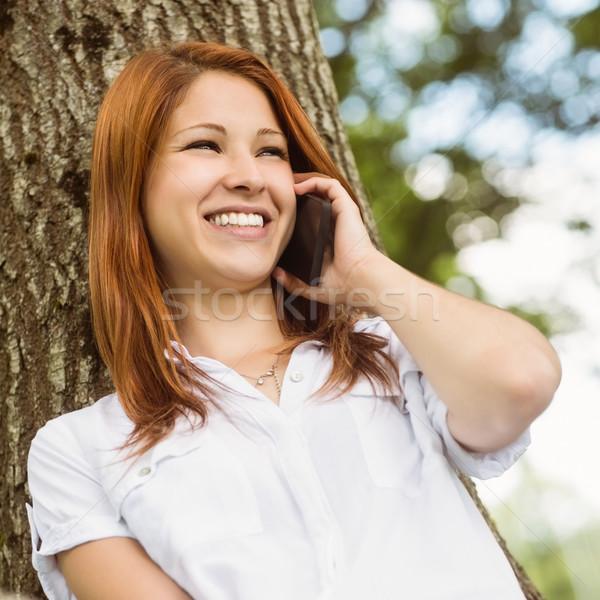 Csinos vörös hajú nő mosolyog telefon park napos idő Stock fotó © wavebreak_media