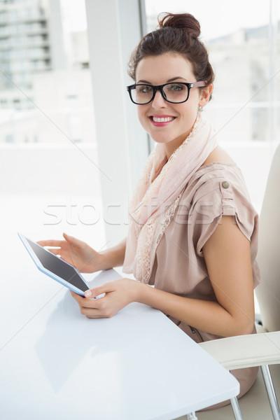 Smiling causal businesswoman using tablet Stock photo © wavebreak_media