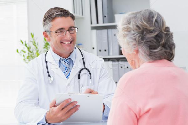 Smiling doctor writing prescriptions for patient Stock photo © wavebreak_media
