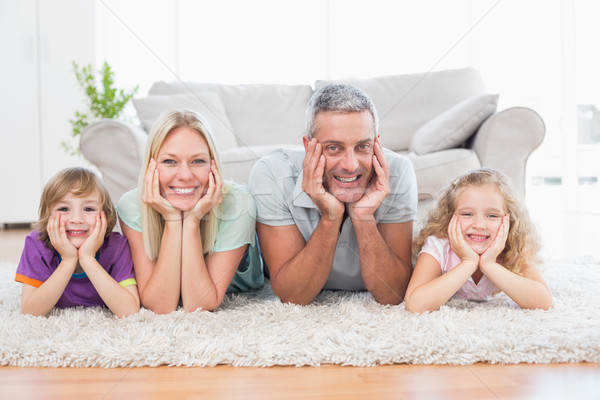 Parents and children with head in hands lying on rug Stock photo © wavebreak_media
