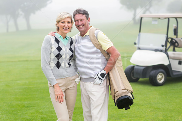 Happy golfing couple with golf buggy behind  Stock photo © wavebreak_media