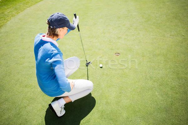 Focused lady golfer kneeling on the putting green  Stock photo © wavebreak_media