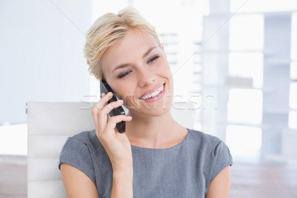 Smiling businessman phoning at her desk  Stock photo © wavebreak_media