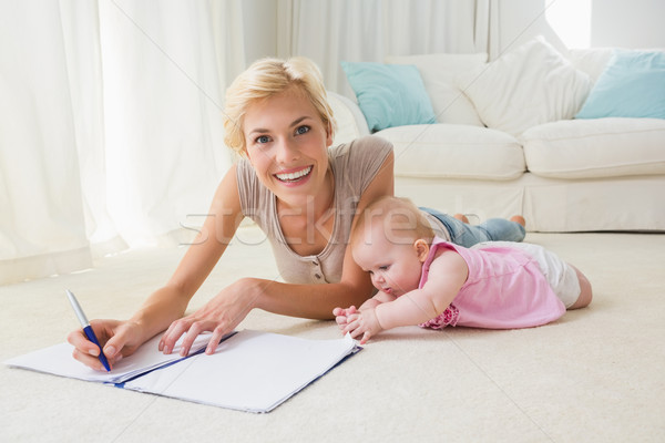 Portrait smiling mother with her baby girl writting on a copyboo Stock photo © wavebreak_media
