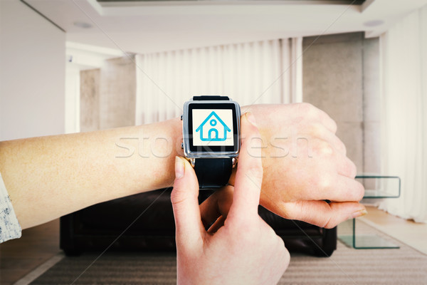 Stock photo: Composite image of woman using smartwatch