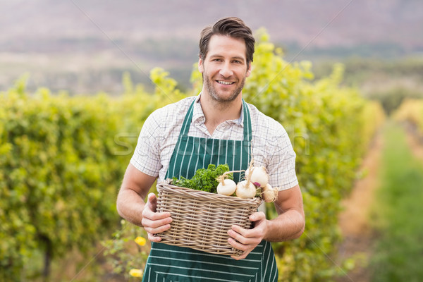 Young happy farmer holding a basket of vegetables Stock photo © wavebreak_media