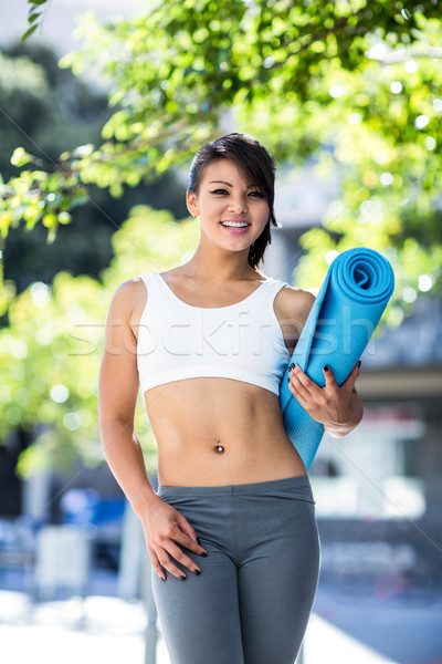 Portrait of smiling athletic woman carrying yoga mat Stock photo © wavebreak_media