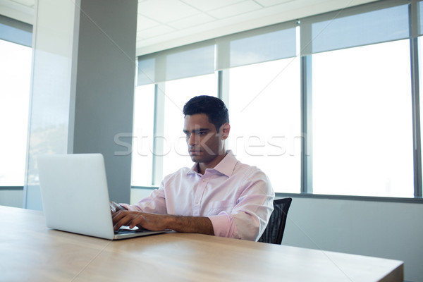 Serious businessman using laptop in conference room Stock photo © wavebreak_media