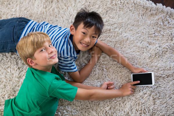 Retrato feliz irmãos tapete telefone móvel sala de estar Foto stock © wavebreak_media