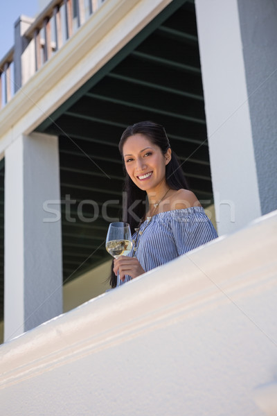 Portrait of woman holding white wine glass in balcony at restaurant Stock photo © wavebreak_media