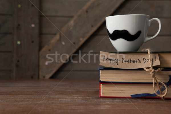 Coffee cup with mustache on stack of books at table Stock photo © wavebreak_media